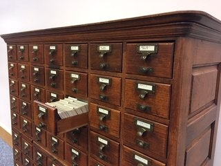 Antique card catalog with open drawer